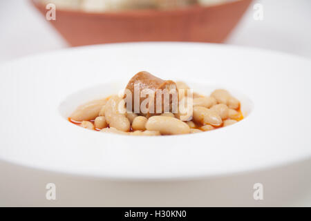 detail view of white circular plate with stew with beans and red sausage, typical spanish food native from Asturias - Stock Photo