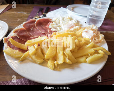 white dish with typical Spain food named huevos rotos or broken eggs with potatoes french fries fried eggs and slices - Stock Photo