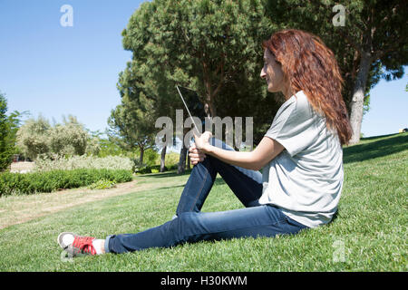 redhead woman blue jeans trousers grey shirt reading digital tablet blank screen sitting on green grass lawn in - Stock Photo