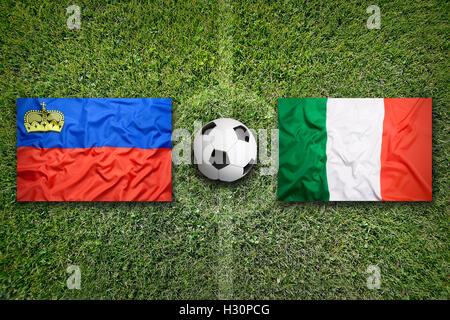 Liechtenstein vs. Italy flags on green soccer field - Stock Photo