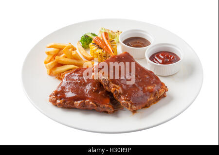 Front view of American style barbecue ribs steak with french fries, grilled vegetables, pepper sauce, and ketchup - Stock Photo