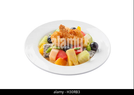 Front view of Modern cuisine style fruits salad with deep fried shrimp in ceramic dish isolated on white background - Stock Photo