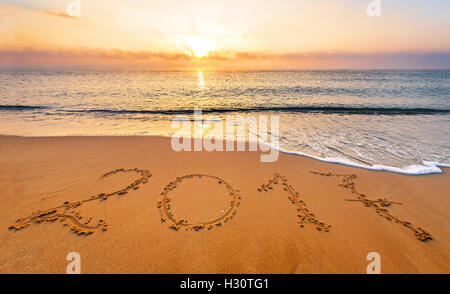 New Year 2017 is coming concept. Happy New Year 2017 replace 2016 concept on the sea beach - Stock Photo