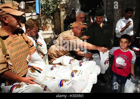 Damascus, Syria. 2nd Oct, 2016. Russian soldiers distribute aid sent from Moscow to afflicted Syrian families in - Stock Photo