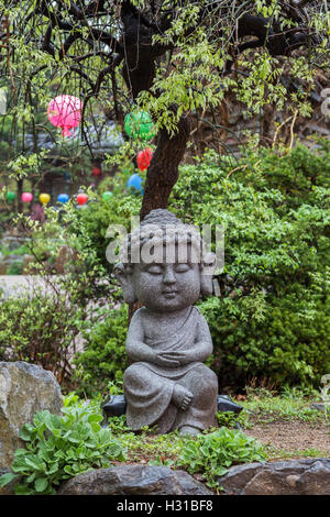 Stone statue of a young sitting Buddha under a tree at the Gilsangsa Temple in Seoul, South Korea. - Stock Photo