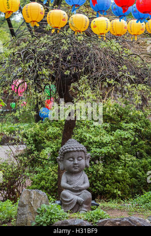 Stone statue of a young sitting Buddha under a tree and colorful lanterns at the Gilsangsa Temple in Seoul, South - Stock Photo
