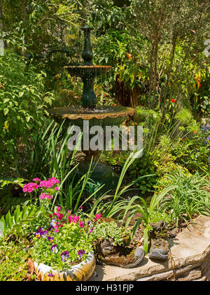 Garden with ornate fountain surrounded by mass of emerald green foliage, trees, & colourful flowers in decorative - Stock Photo