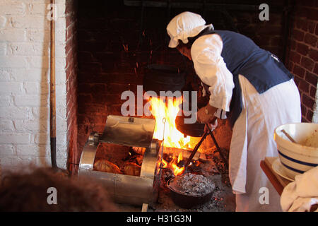 Demonstration of old style cooking in fireplace - Stock Photo