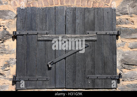 Wooden vintage shutter on closed and locked window with iron padlock on stone wall - Stock Photo
