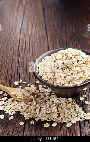 Oatmeal in black bowl and near on dark wooden table - Stock Photo