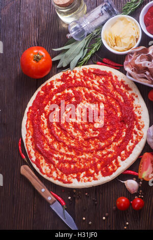 pizza and ingredients on the wooden table - Stock Photo