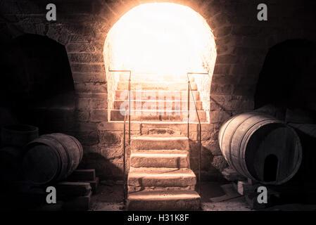 Wine cellar stone stairs leading up towards bright light - Stock Photo
