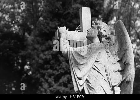 Statue of an angel carrying a cross tombstone gravestone at Highgate Cemetery East in London, England. - Stock Photo