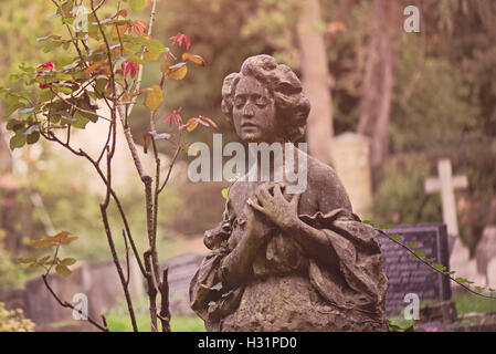 Gravestone tombstone statue of a woman in deep sorrow at Highgate Cemetery East in London, England. - Stock Photo