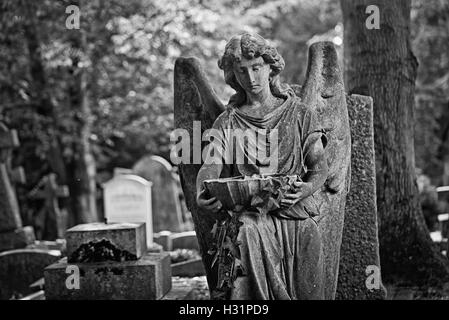 Angel with stone water chalice gravestone tombstone at Highgate Cemetery East in London, England. - Stock Photo