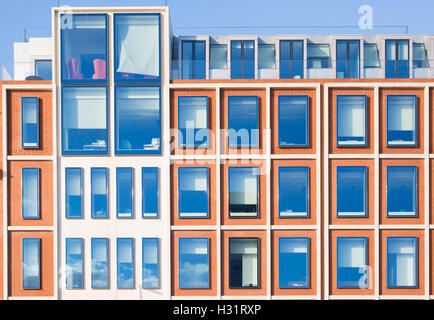 Exterior of modern apartment building in red bricks with white finish. Blue sky reflected in glass windows - Stock Photo