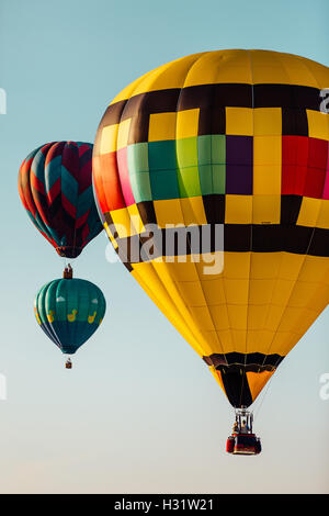 Three colorful hot air balloons isolated against a clear sky - Stock Photo