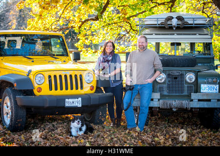A man and woman standing in front of a Jeep Wrangler and a Land Rover with a border collie. - Stock Photo