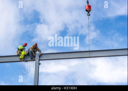 Iron workers sitting on a beam at a construction site - Stock Photo