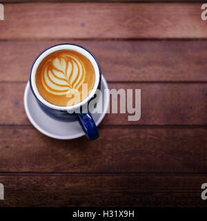 Cup of Coffee Latte on Wooden table with Natural light, selective focus on a cup - Stock Photo
