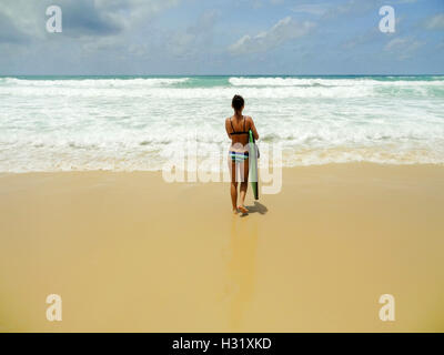 a happy young surf woman runing at the beach with a surfboard - Stock Photo
