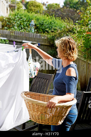 Woman hanging out clothes washing on outdoor rotary line in her garden - Stock Photo
