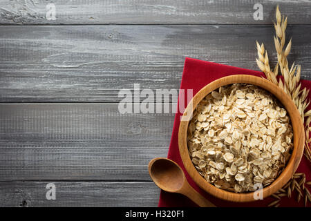 bowl of oat flakes at wooden background - Stock Photo