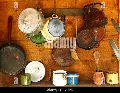 Scratched and damaged old frying pans and cooking pots hanging on a wooden wall - Stock Photo