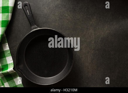 frying pan and napkin on black background - Stock Photo