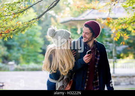 Young couple having fun together outdoors. The man is holding a smartphone while his girlfriend is jumping on his - Stock Photo