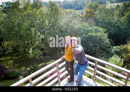 Young couple taking a selfie on their garden balcony using a smart phone. - Stock Photo