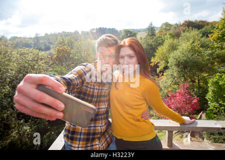 Young couple taking a silly selfie on their garden balcony, using a smart phone. - Stock Photo