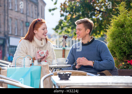 Young couple enjoying a cup of tea at a cafe together. they are sitting outdoors in the city. - Stock Photo