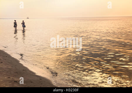Two girls walking on sea water coast at summer - Stock Photo