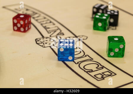 Playing Dice on a board inside of the Cardiff Arcades store Rules of play. - Stock Photo