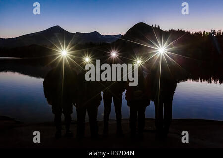 Group of five hikers with headlamps at deep twilight along Lake of the Woods, in the Desolation Wilderness, California, - Stock Photo