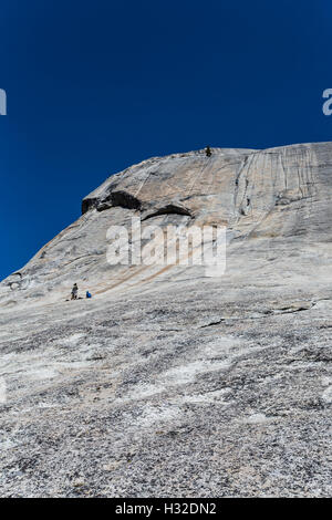 Rock climbers on Lembert Dome in Yosemite National Park, California, USA - Stock Photo