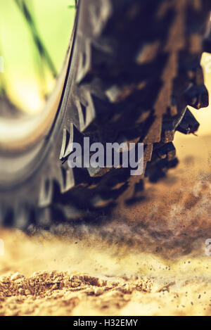 Mountain bike wheel close up with dirt dust particles, MTB bicycle ride through sandy ground - Stock Photo
