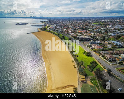 Aerial view of Brighton Beach coastline with Melbourne CBD skyscrapers in the distance - Stock Photo