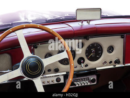 Dashboard of an old classic car with round measuring instruments and wooden steering wheel - Stock Photo