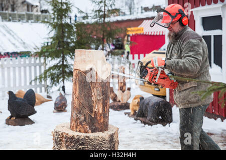 Hamina, Finland - December 13, 2014: Professional Finnish sculptor with a chainsaw produces wooden bird sculpture - Stock Photo