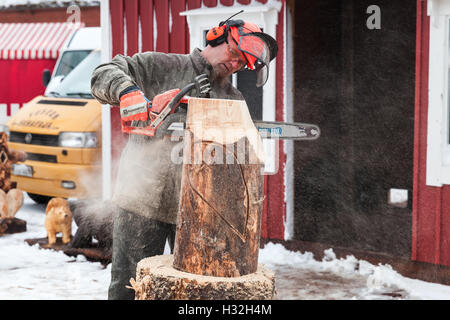 Hamina, Finland - December 13, 2014: Master sculptor with a chainsaw produces wooden bird sculpture - Stock Photo