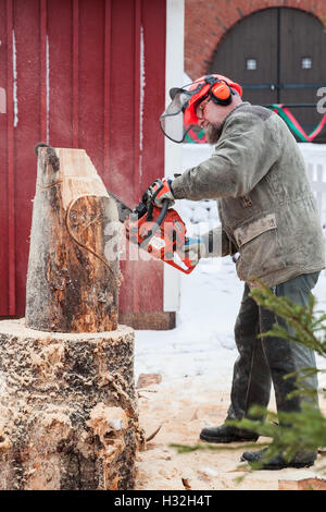 Hamina, Finland - December 13, 2014: Finnish master sculptor with a chainsaw produces wooden sculpture - Stock Photo