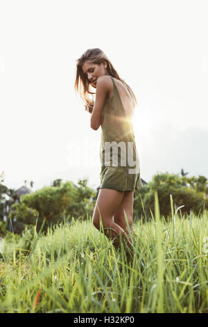 Full length shot of attractive young woman in field with sun shining in background. Female fashion model outdoors - Stock Photo