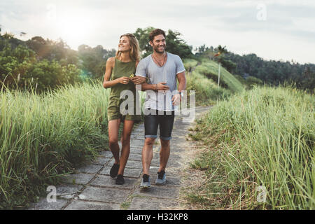 Outdoor shot of young couple in love walking on pathway through grass field. Man and woman walking along tall grass - Stock Photo