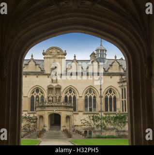 Ornate entrance to Oriel college in Oxford, with  view through dark archway to 17th century gothic style building - Stock Photo