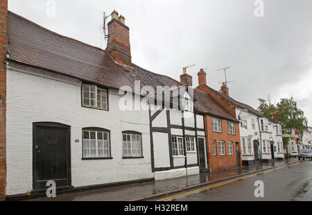 Row of historic black and white medieval buildings beside more modern red brick building in Stratford-upon-Avon, - Stock Photo