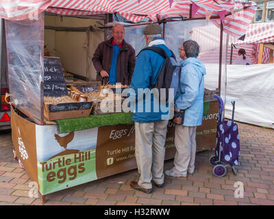 Customers buying eggs on a specialist farmer's market stall in North Yorkshire - Stock Photo