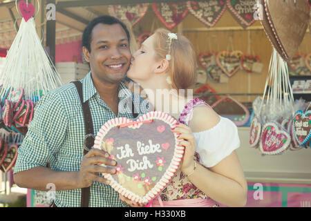 In love interracial couple enjoying Oktoberfest - Stock Photo