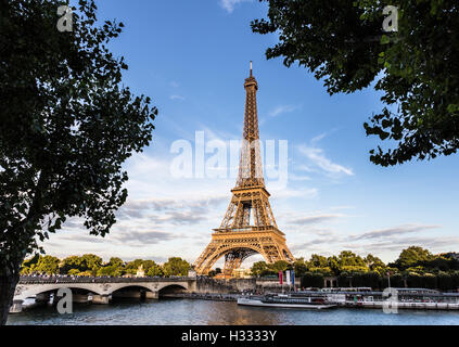 Sunset over the Eiffel Tower along the Seine river in Paris, France capital city. - Stock Photo